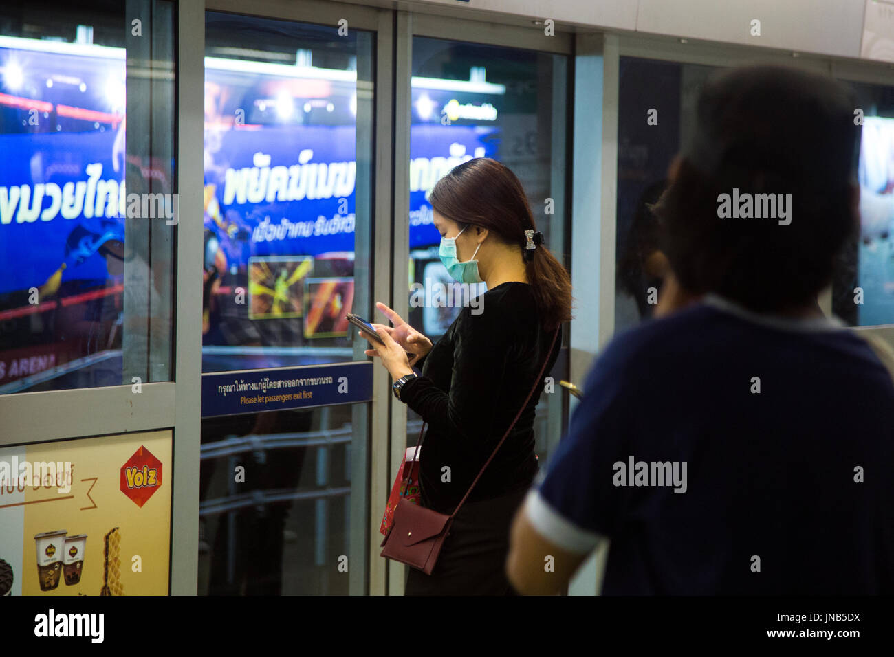 Woman on her mobile phone wearing an anti-pollution mask in the Bangkok subway, Thailand - Stock Image