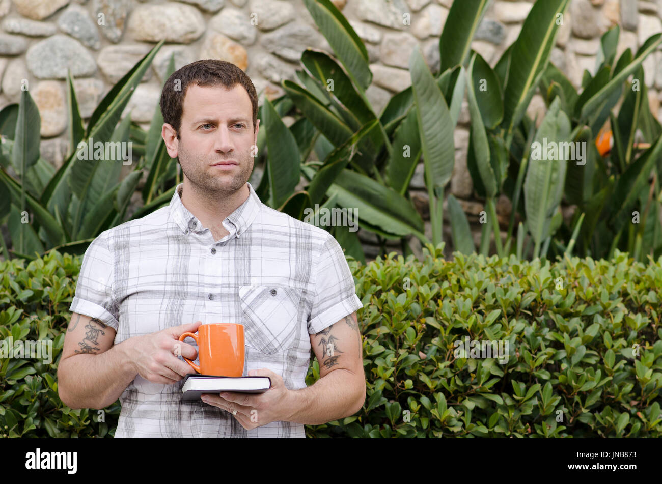 Man thinking of what tomorrow brings holding a book and coffee mug. - Stock Image