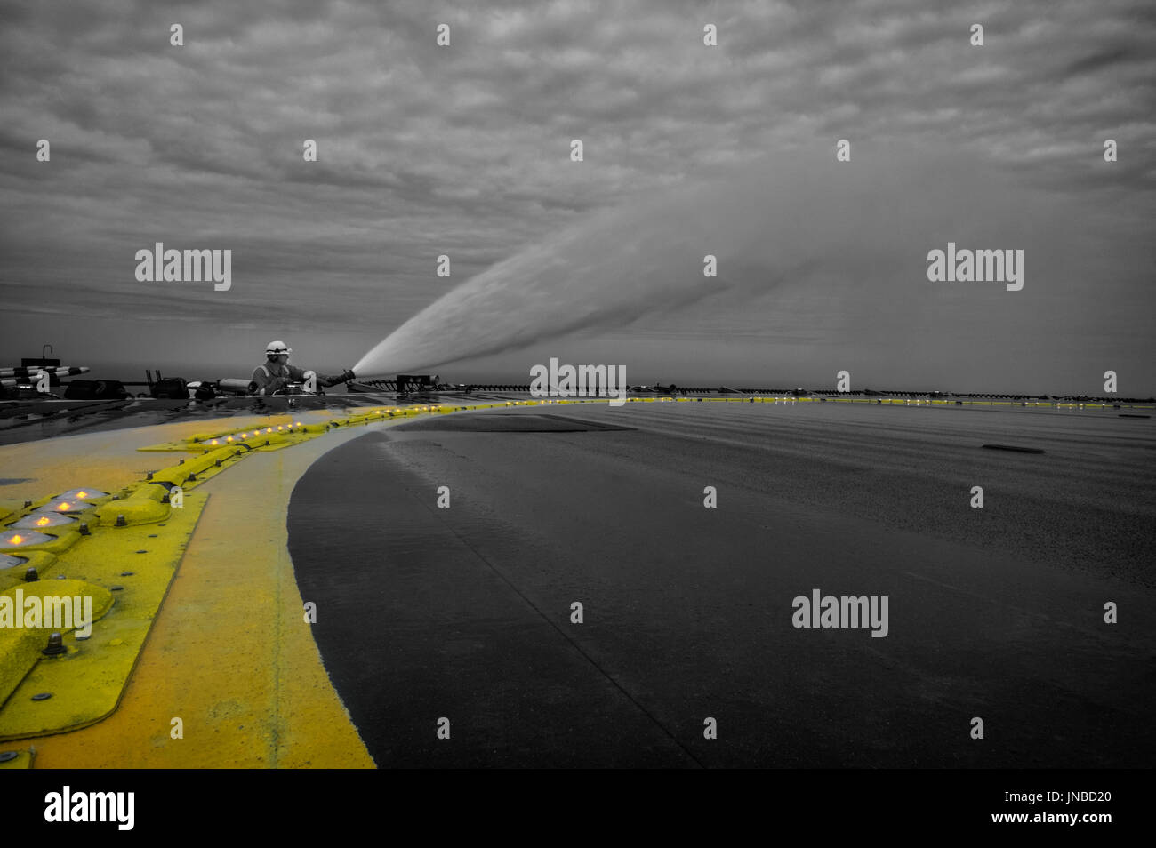 Offshore Heli deck assistant, testing the fire water monitors, credit: LEE RAMSDEN / ALAMY - Stock Image