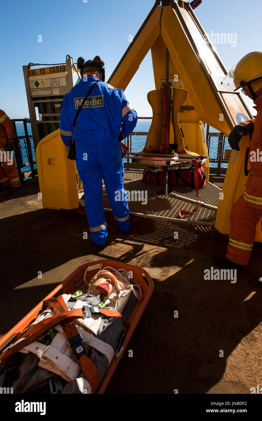 A medic with blue coveralls/overalls, Dummy casualty on a stretcher about to be loaded into the frog. credit: LEE RAMSDEN / ALAMY - Stock Image