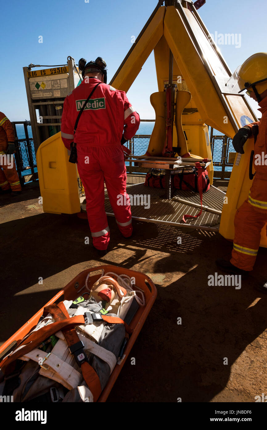 A medic with red coveralls / overalls  Dummy casualty on a stretcher about to be loaded into the frog. credit: LEE RAMSDEN / ALAMY - Stock Image
