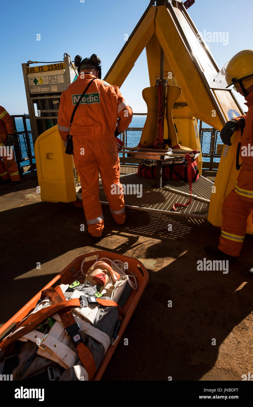 A medic with orange coveralls / overalls, Dummy casualty on a stretcher about to be loaded into the frog. credit: LEE RAMSDEN / ALAMY - Stock Image
