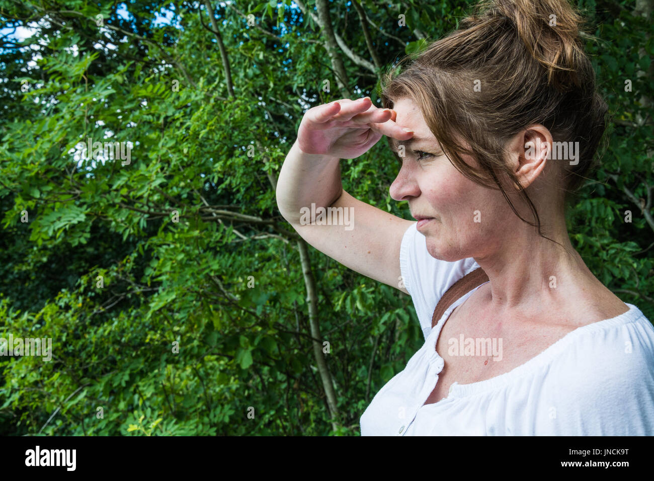 A woman shading her eyes to get a clearer view. A looking concept, as in looking ahead, to the future, looking out for obstacles and dangers. UK - Stock Image