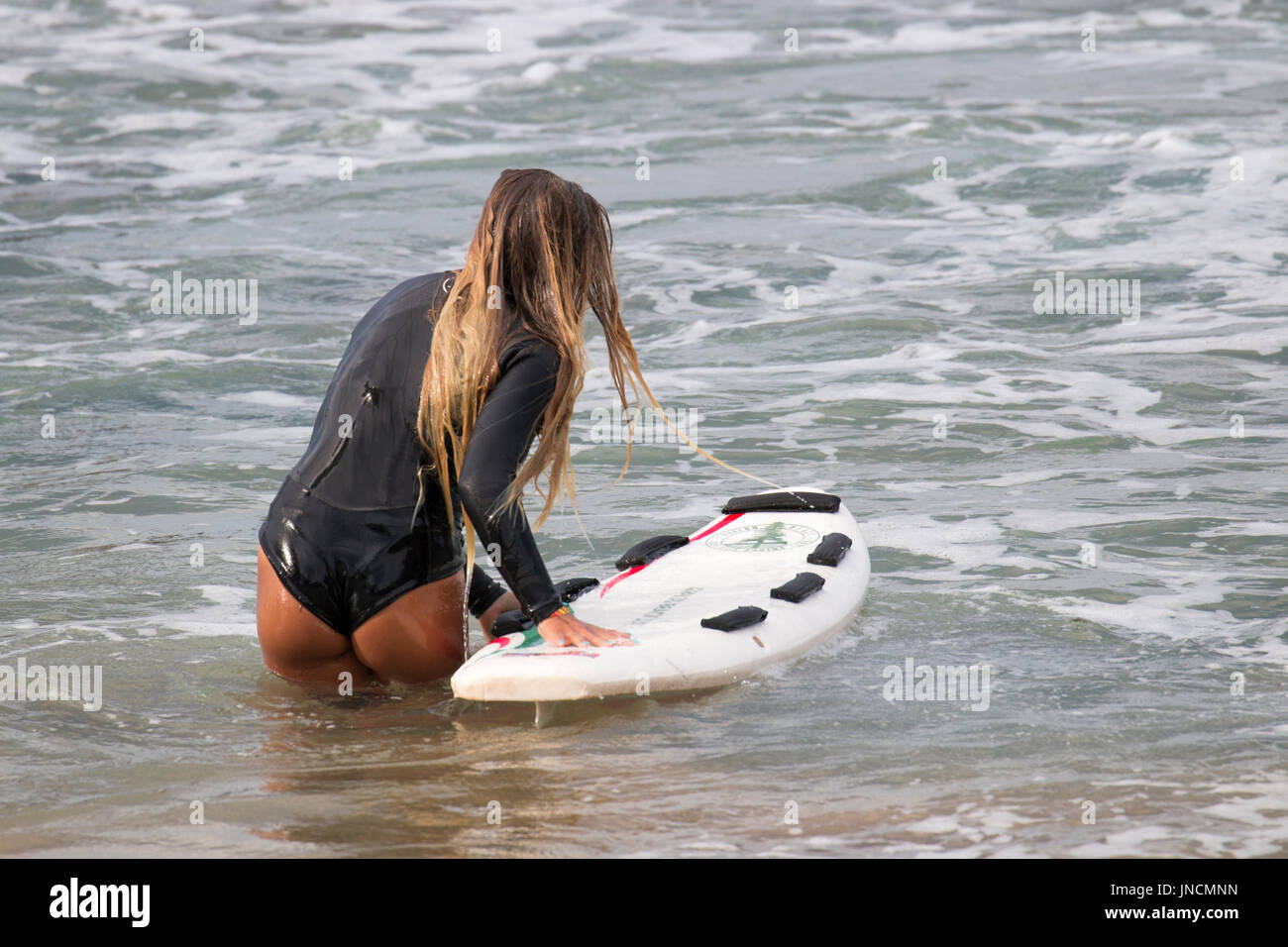 Australian girl in Sydney at the beach with surfboard surfing in the ocean,Sydney,Australia - Stock Image