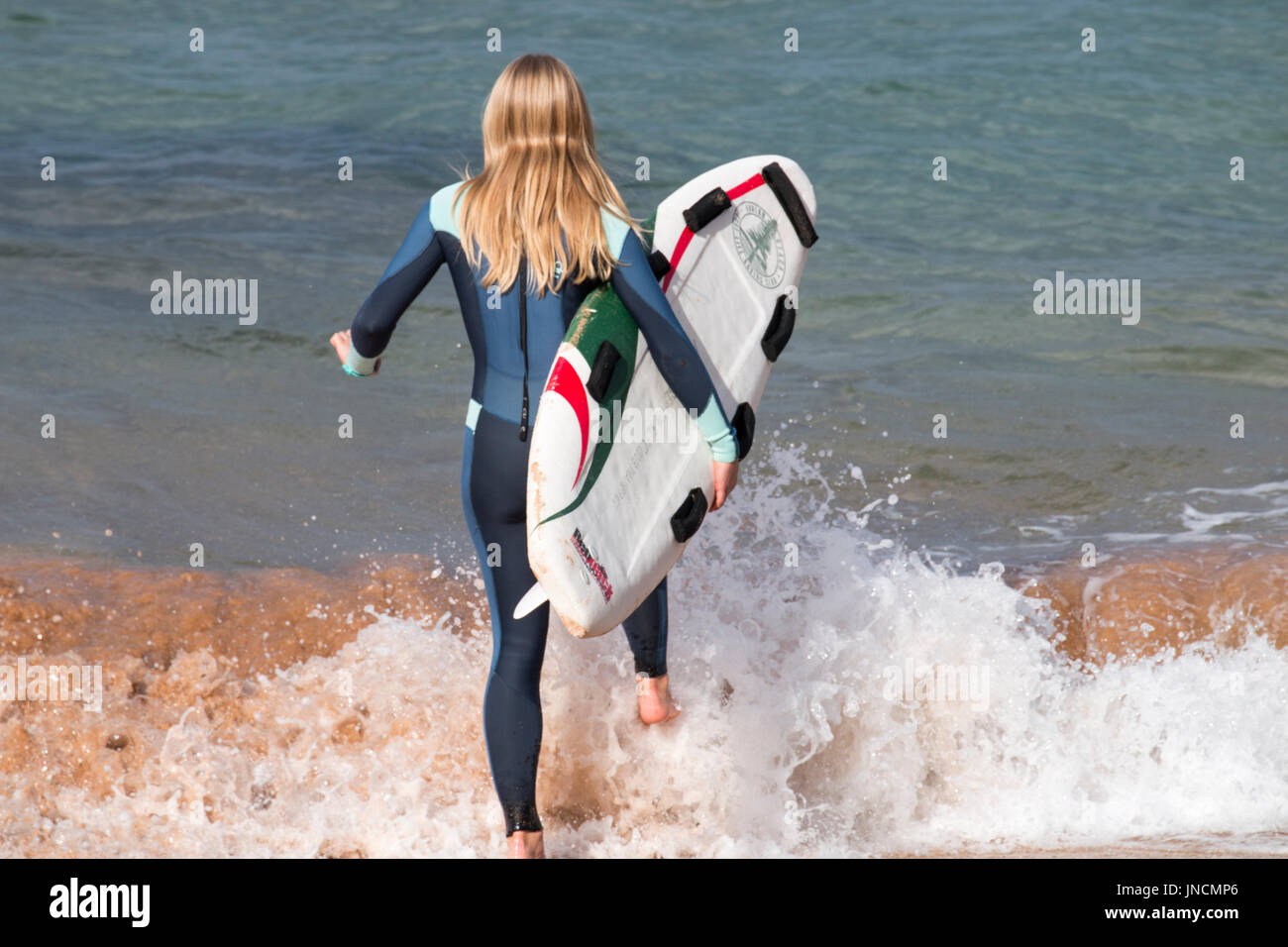 Young woman girl carrying her surfboard out to sea for a surf, Sydney,Australia - Stock Image
