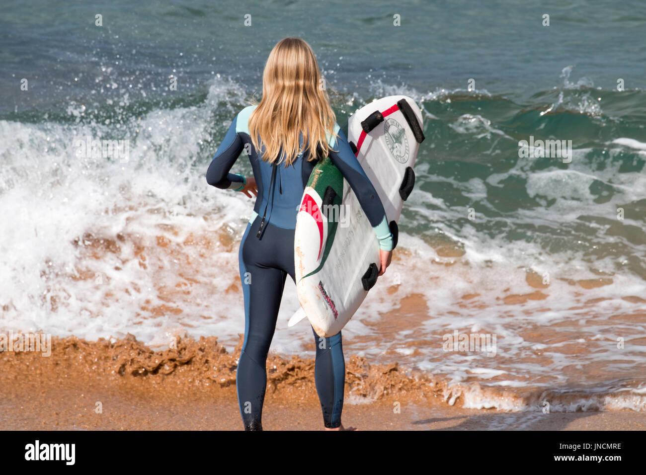 Rear view of blonde australian girl stood on a beach holding her surfboard,Sydney,Australia - Stock Image