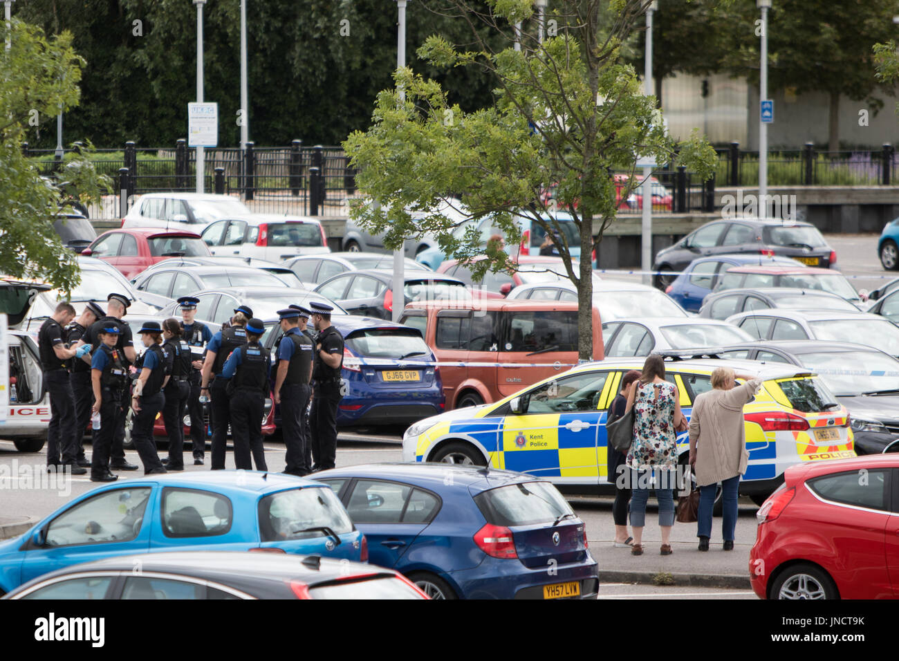 A man has been arrested after allegedly slitting a woman's throat in a busy shopping centre car park this morning Stock Photo