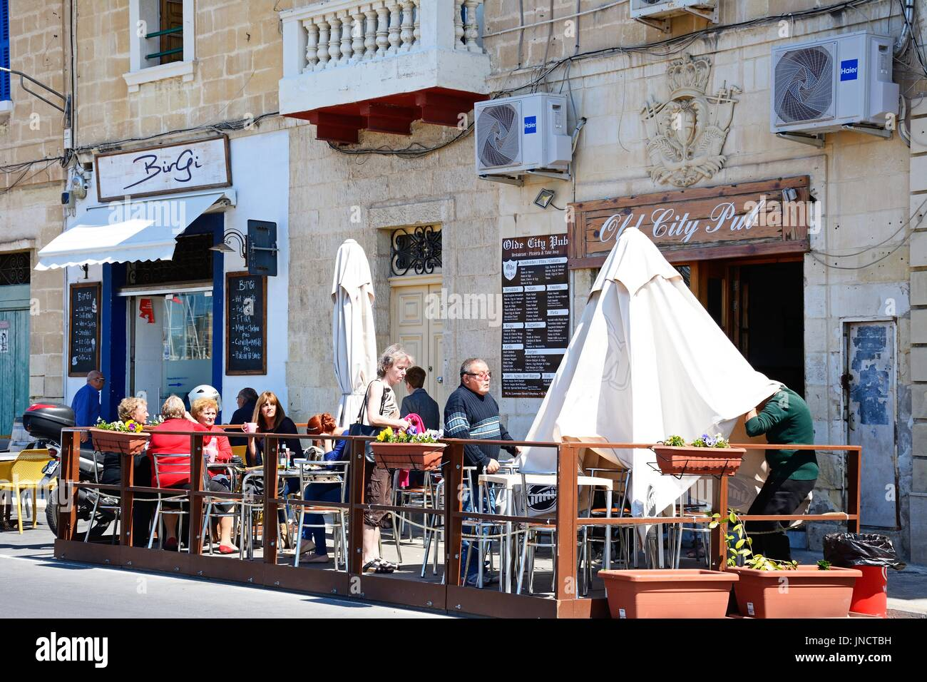 Tourists relaxing at a pavement cafe along the waterfront, Vittoriosa (Birgu), Malta, Europe. - Stock Image