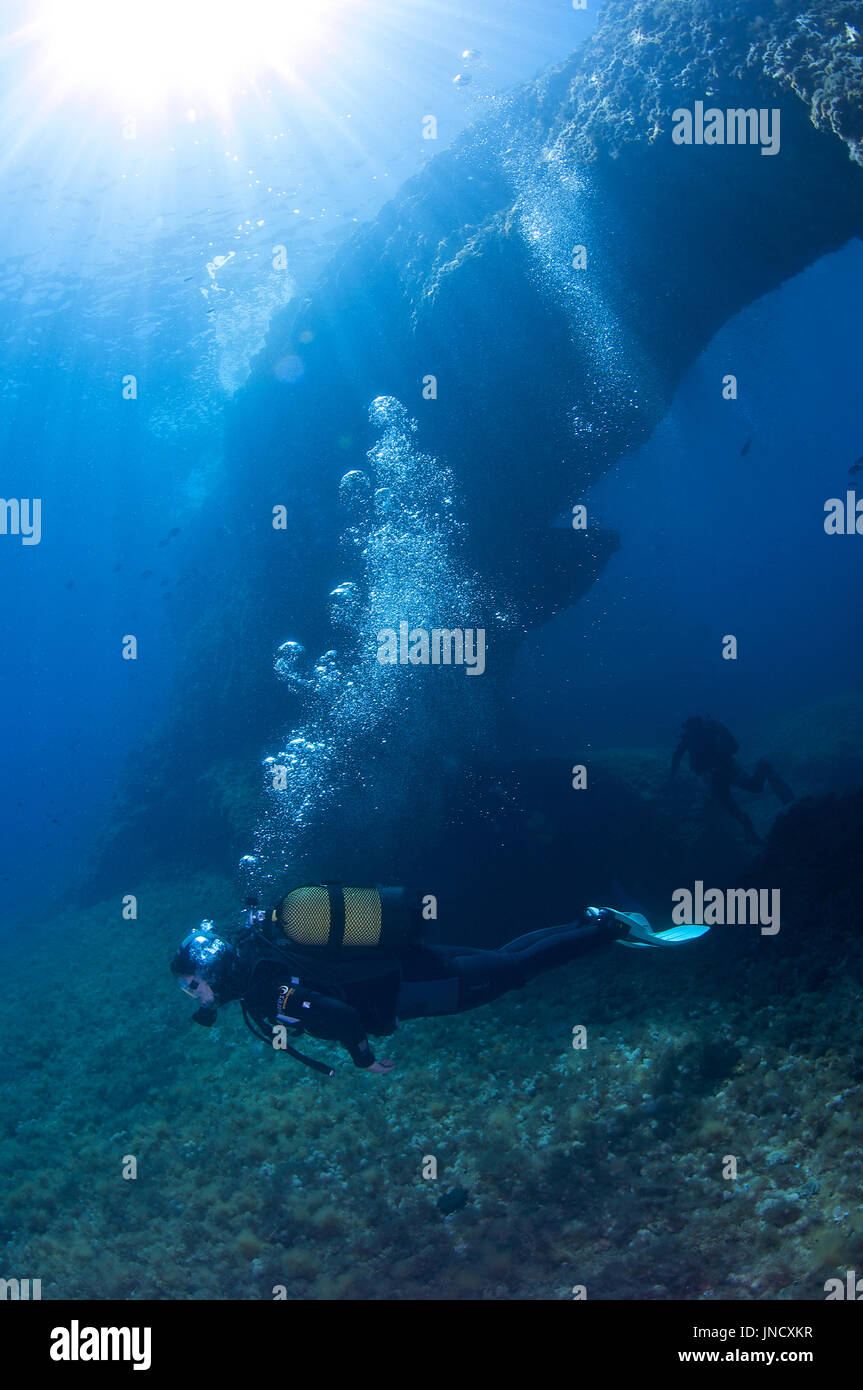 Scuba diver at 'El Arco' dive site at Ses Salines Natural Park at Formentera (Balearic Islands, Spain) - Stock Image