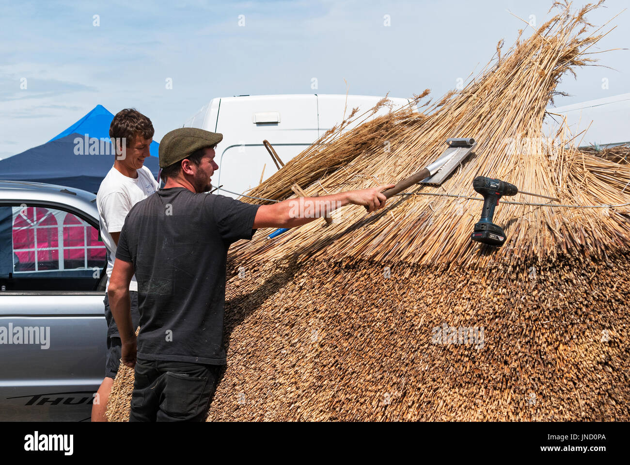 roof thatchers giving an exhibition of thatching skills at a country fair in cornwall, england, uk. - Stock Image