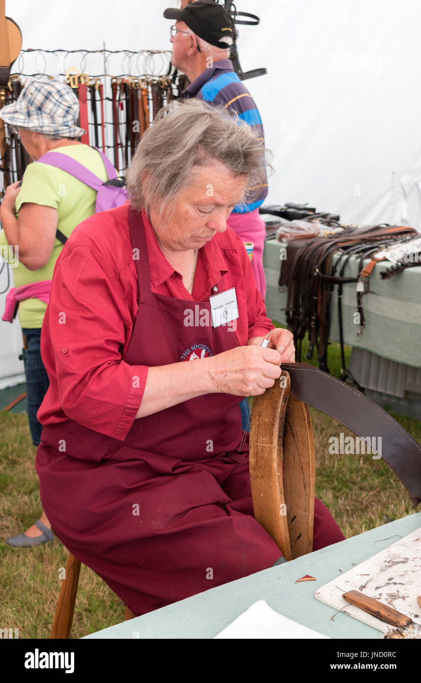 a saddle and harness maker at a countryside and rural skills exhibition in cornwall, england, uk. - Stock Image