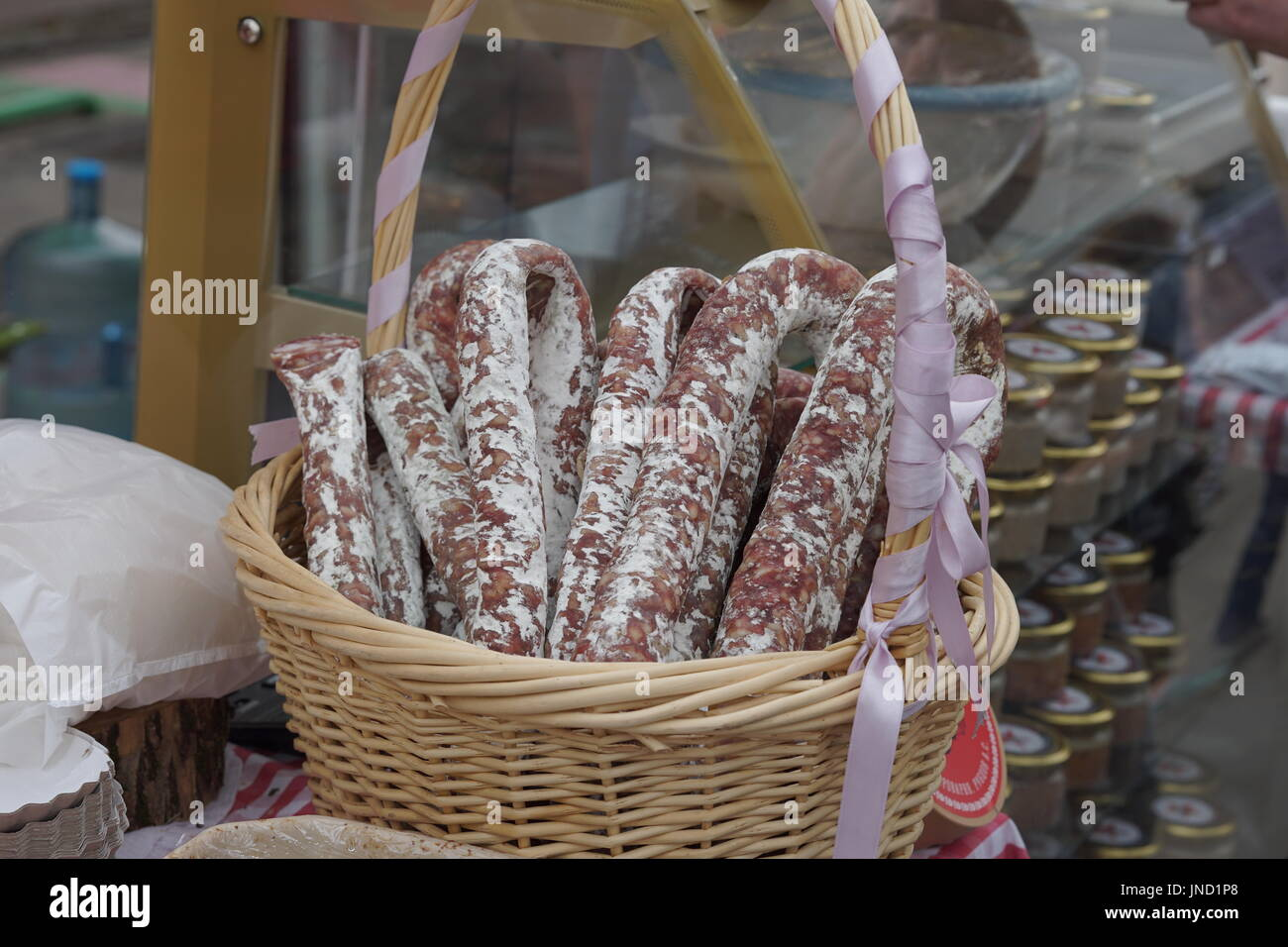 Wicker basket of italian sausage - traditional handmade organic salami in market. Gastronomic products for gourme - Stock Image