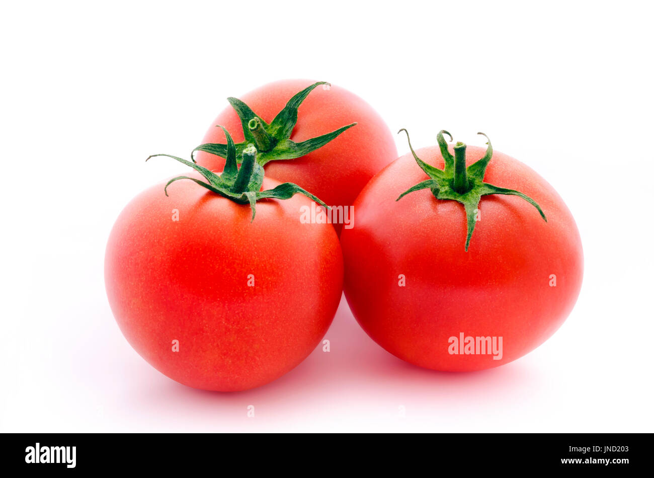 Three fresh raspberry tomatoes isolated on white background - Stock Image