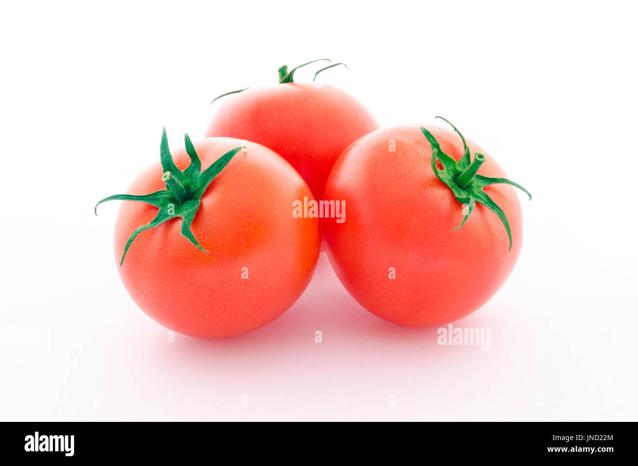 Three juicy tomatoes isolated on white background - Stock Image