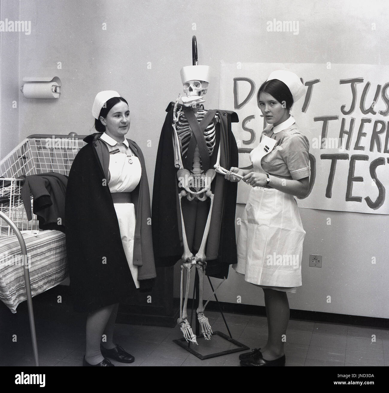 1970s, historical, two female nurses with a model of a human skeleton with a nurse's cloak and hat on and a sandwich pressed into its mouth.The nurses were using the skeleton to make a point in their protest about trying to live and survive on low wages. - Stock Image