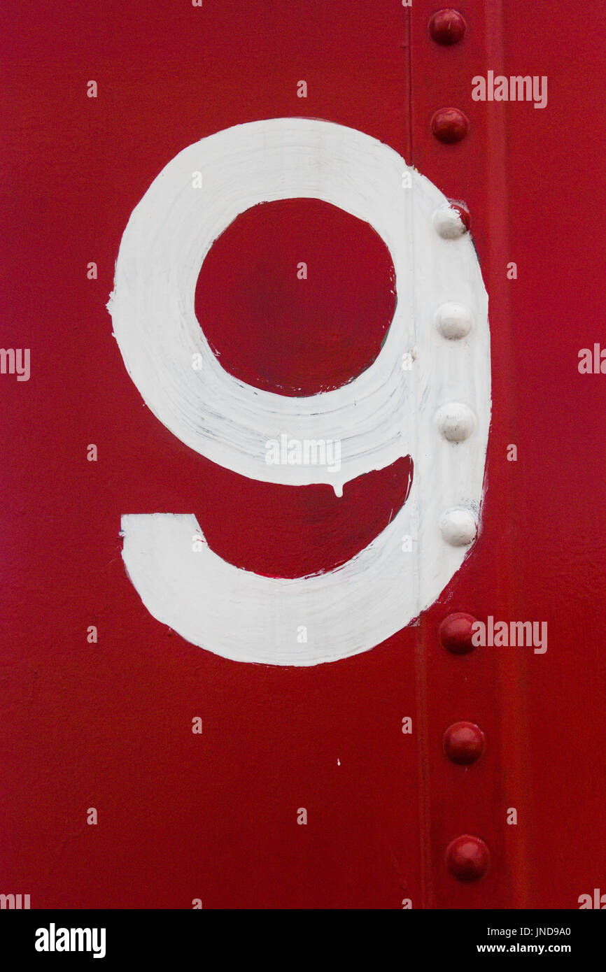 White numeral 9 painted on the side of a red railroad car - Stock Image