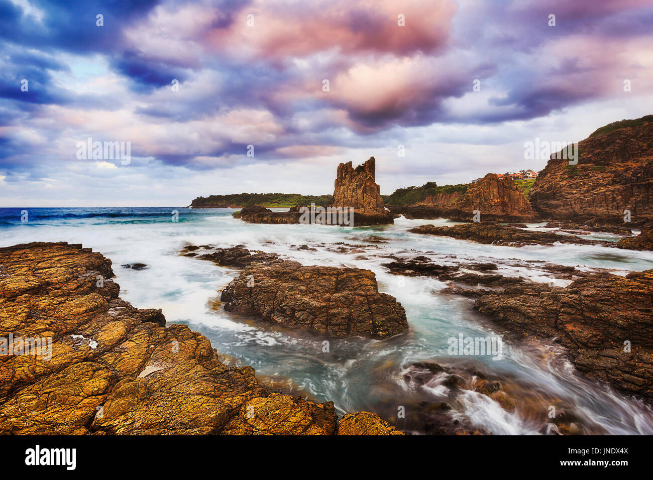 Rugged rocky coast around bombo beach in Kiama town on Australian Pacific shore. Blurred surf flows ashore eroding sandstone cliffs and cathedral boul - Stock Image