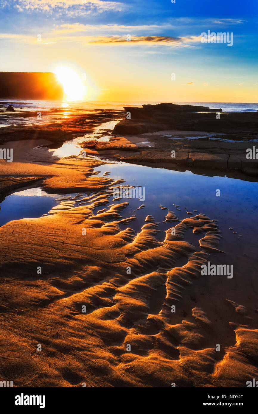 Bright warm rising sun over Royal National park headland from Garie beach sea floor of Pacific coast, Australia. - Stock Image
