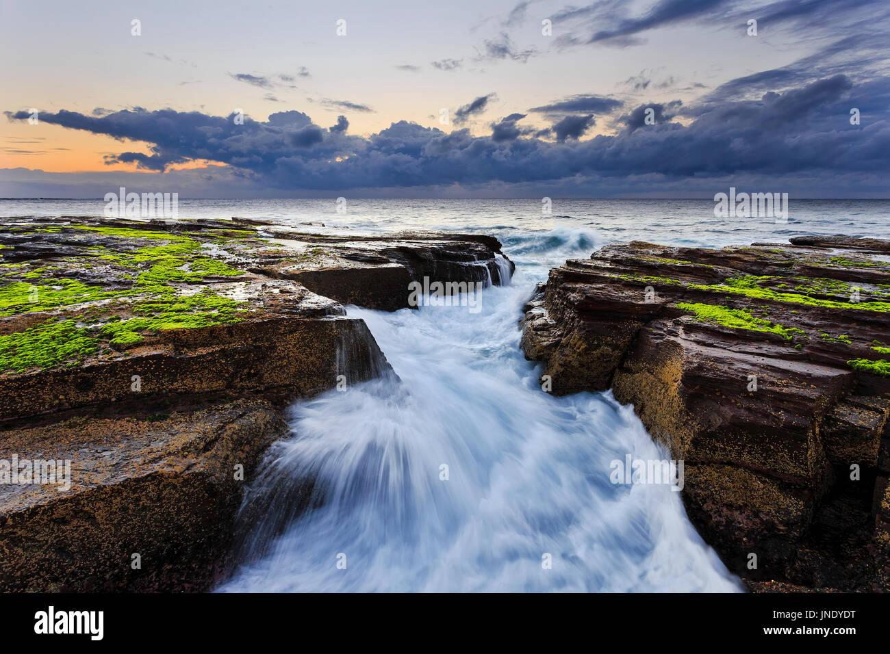 Crack in coastal rocks of Pacific ocean when inbound wave flows through between sandstone boulders at sunrise. - Stock Image