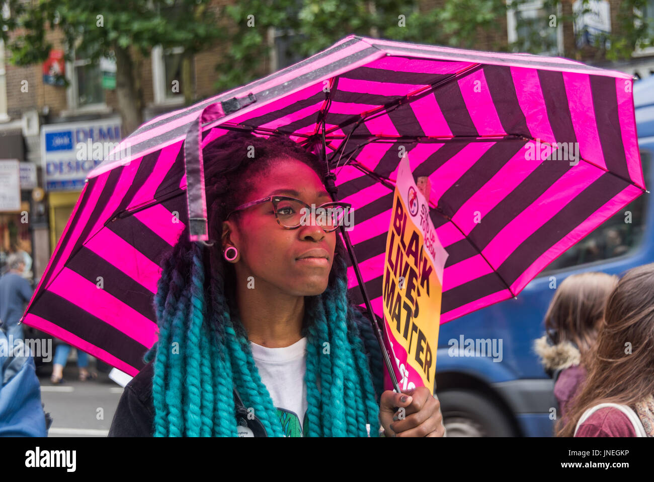 July 29, 2017 - London, UK - London, UK. 29th July 2017. A woman with a pink striped umbrella holds a Black Lives - Stock Image