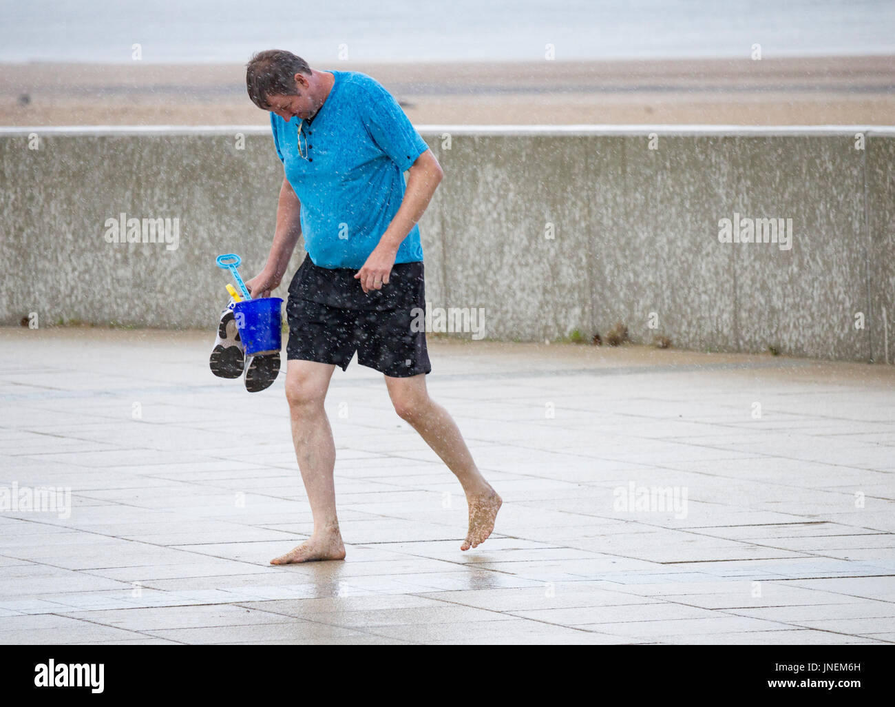 Seaton Carew, county Durham, England, UK. 30th July, 2017. Weather: Sunshine and heavy showers at Seaton Carew on the north east coast on Sunday afternoon. PICTURED: people run from the beach as a heavy rain shower replaces the warm sunshine. Credit: ALAN DAWSON/Alamy Live News - Stock Image