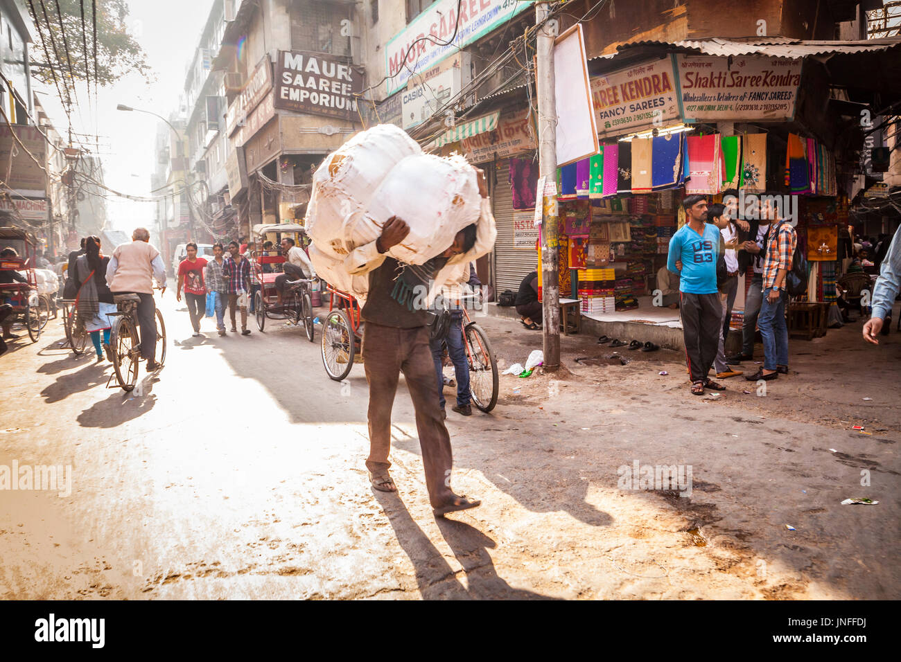 A man carrying a heavy and awkward load on his shoulders through the streets of Chandni Chowk, one of the busiest and oldest markets in Delhi, India. - Stock Image
