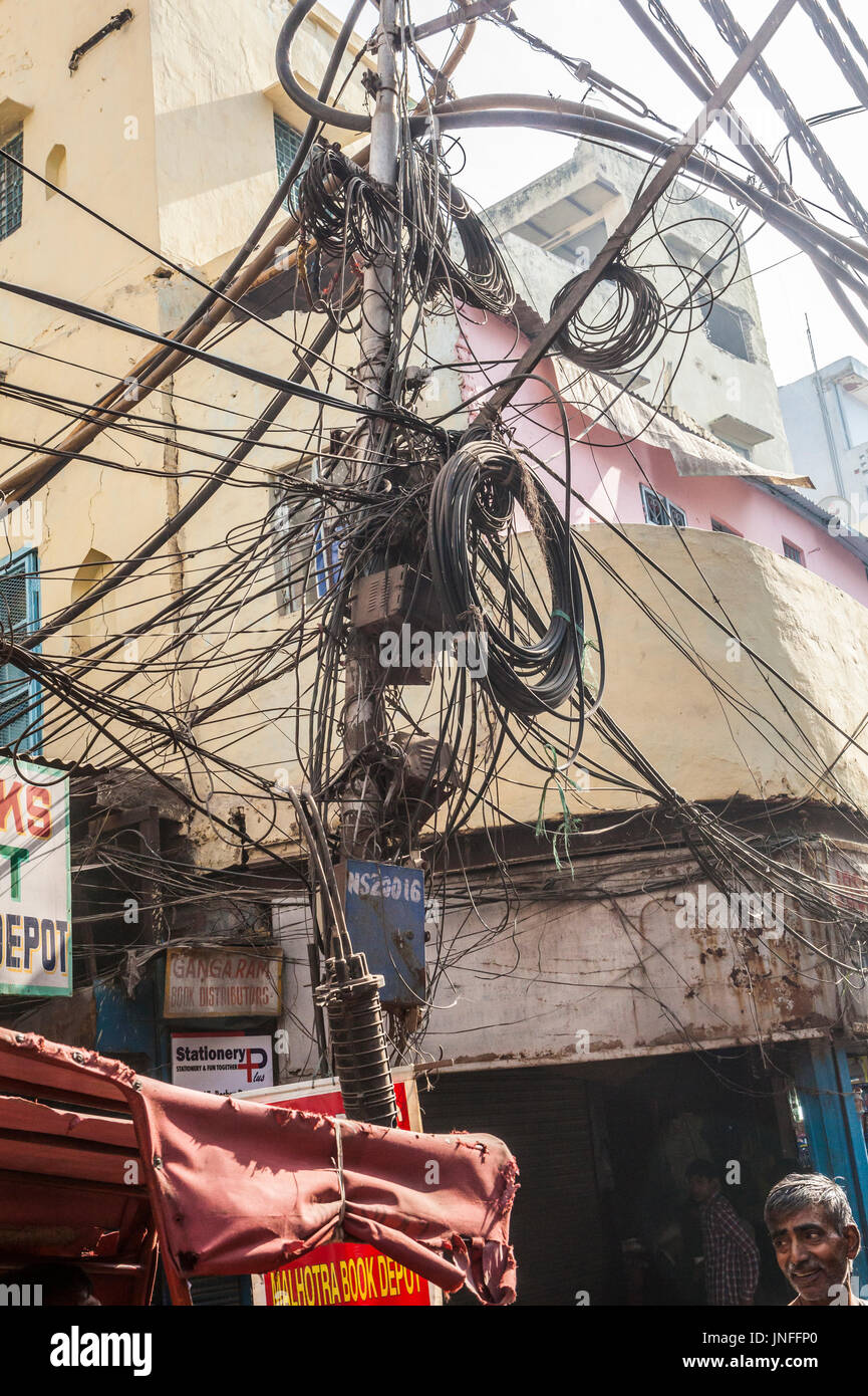 A tangle of utility wires and cables above the streets in Chandni Chowk, a wholesale market in Old Delhi, India. - Stock Image