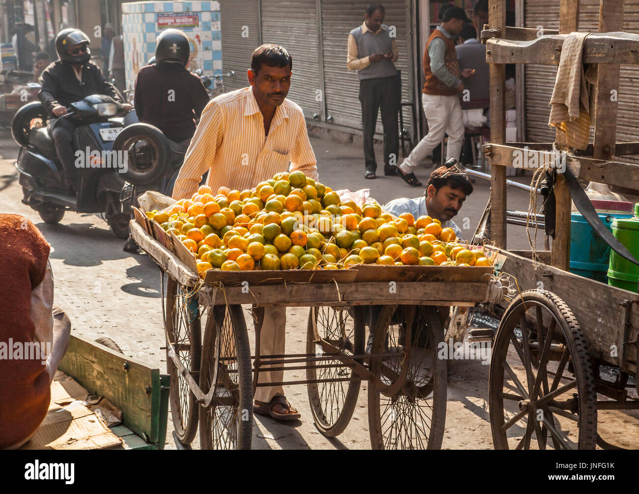 A man in the street pushing his cart of peeled and unpeeled oranges, Chandni Chowk, Old Delhi, India. - Stock Image