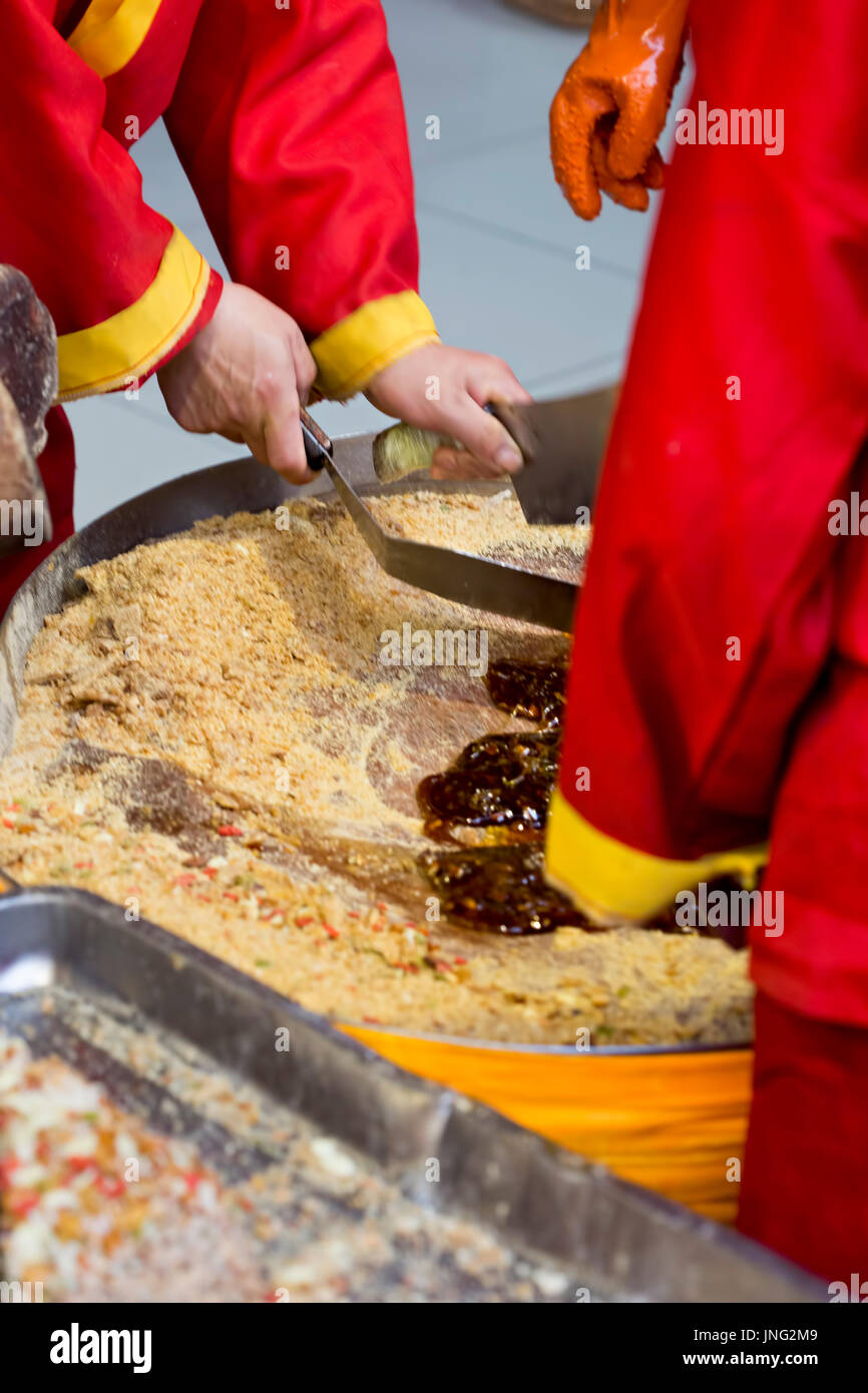 Group of Chinese workers making and selling caramel sweets, Beijing market, China Stock Photo