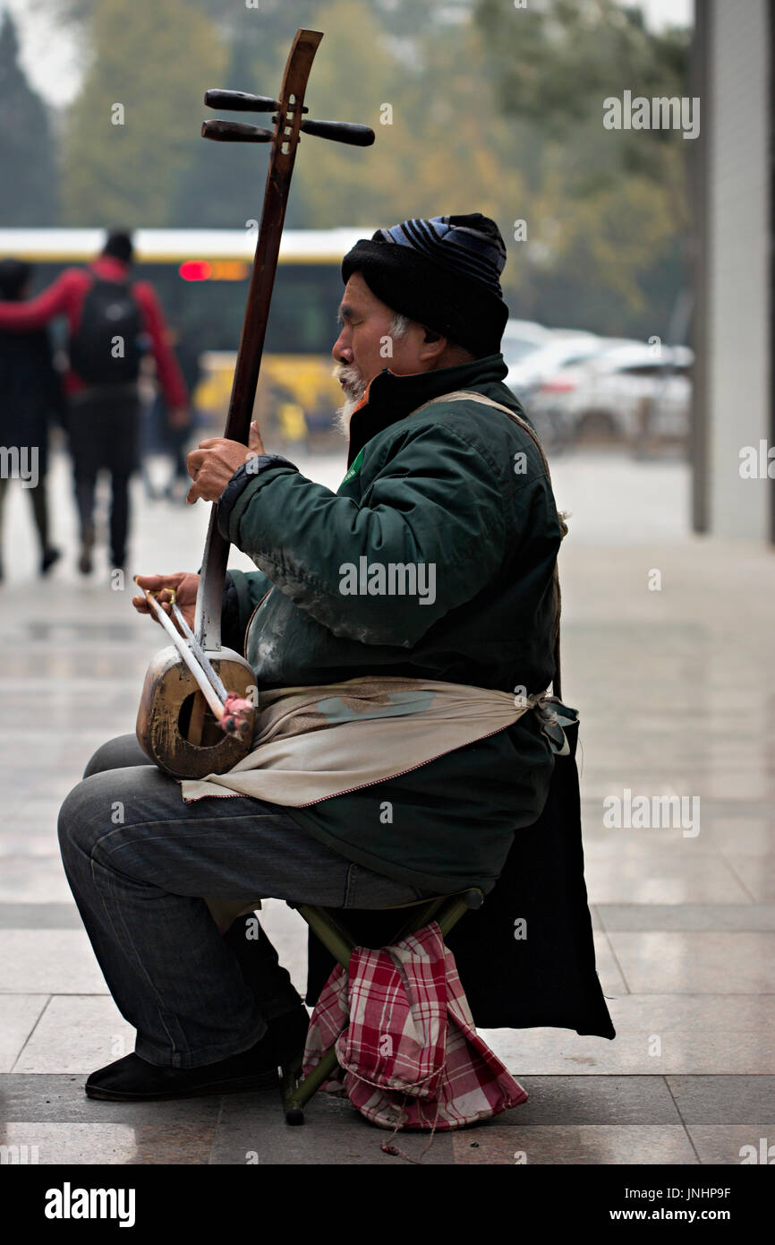 Chinese old musician playing on the street on sanxian lute - a three stringed fretless plucked musical instrument - Stock Image