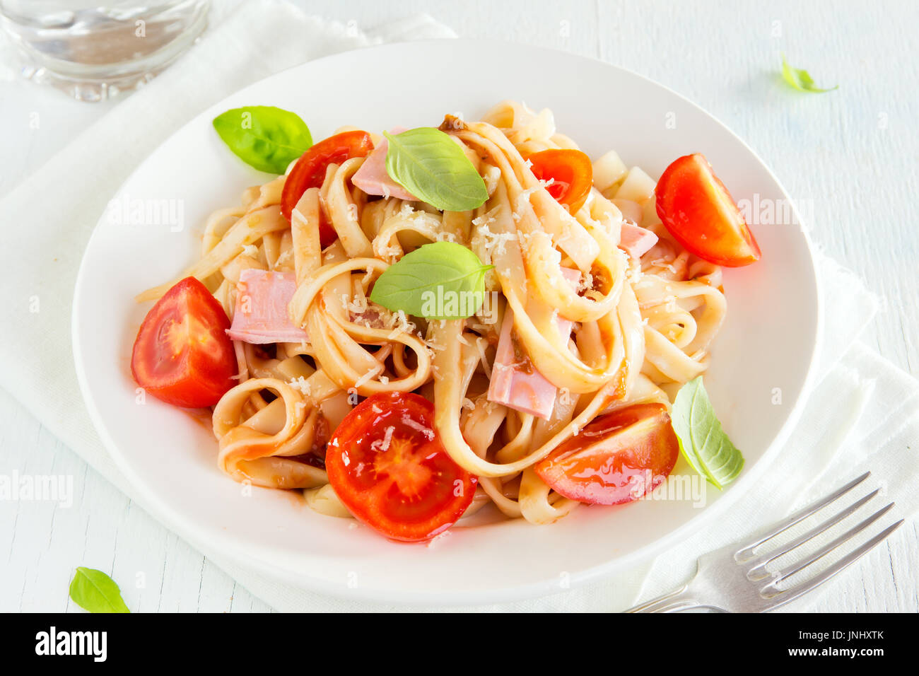 Tagliatelle pasta with ham, tomato sauce, cherry tomatoes and basil leaves on white plate - homemade delicious tagliatelle - Stock Image