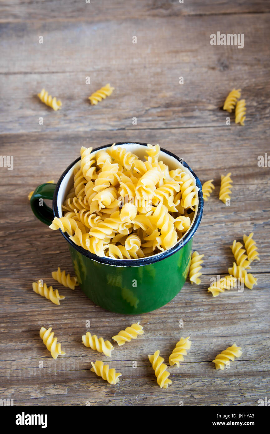 Tagliatelle pasta with ham, tomato sauce, cherry tomatoes and basil leaves on white plate - homemade delicious tagliatelle pasta - Stock Image
