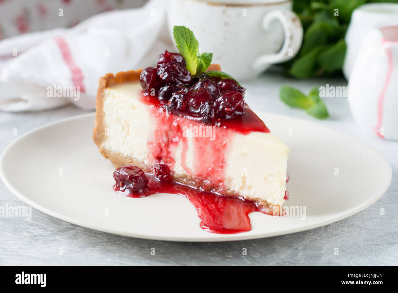 Slice of new york cheesecake with cherry sauce and mint leaf on top. - Stock Image