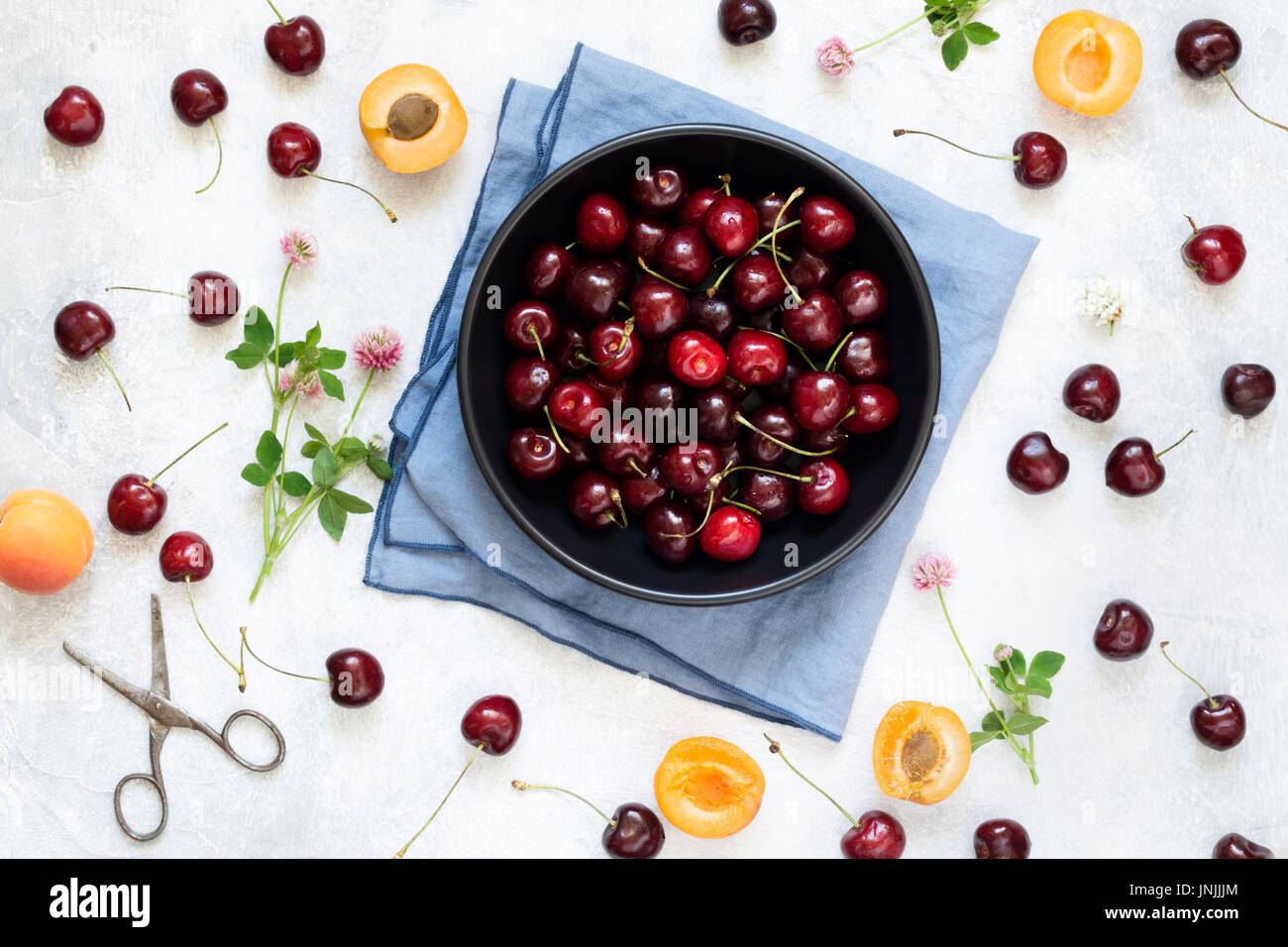 Berry flat lay with sweet cherries, apricots and clover leaf on white background, top view - Stock Image