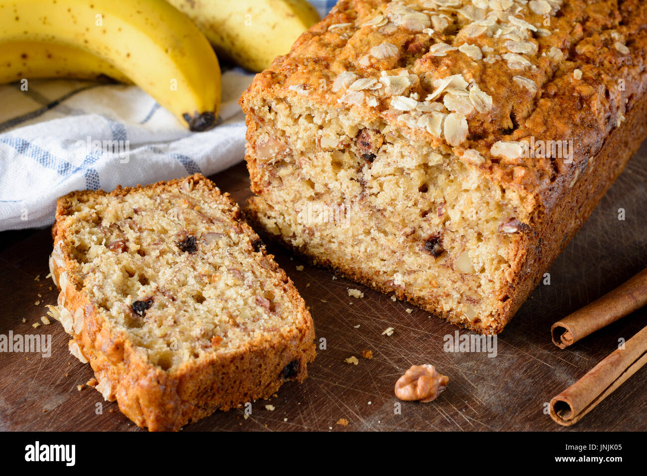 Protein banana bread loaf with walnuts and cinnamon on wooden board. Closeup view - Stock Image