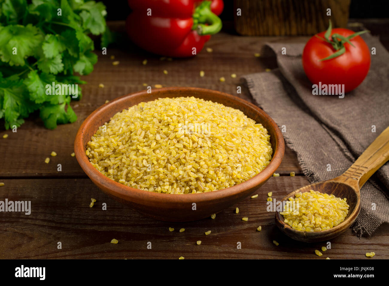 Bulgur Gluten Free Wheat Grains in bowl on wooden table - Stock Image