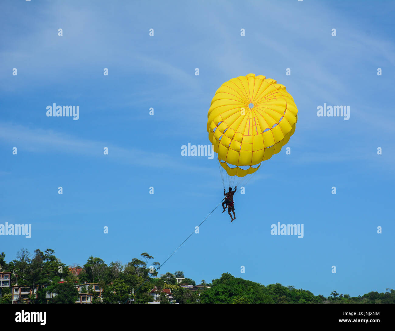 People playing parasailing in Phuket, Thailand. Phuket is a heady mix of bustling bars, night spots, restaurants and truly spectacular dive locations. - Stock Image