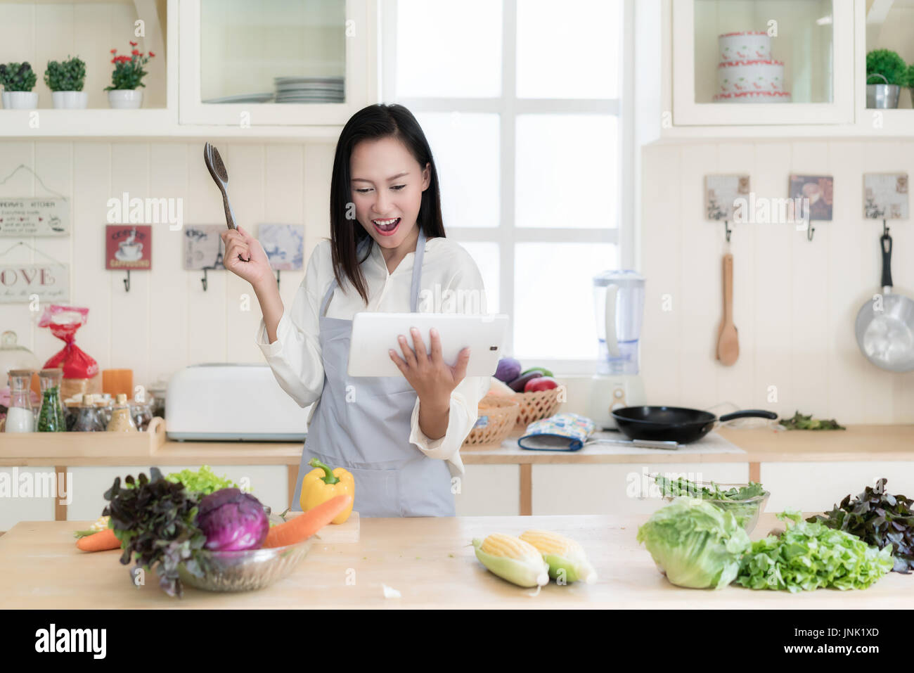 cheerful asian young woman is cooking in the kitchen with joy she is standing and - Cooking In The Kitchen