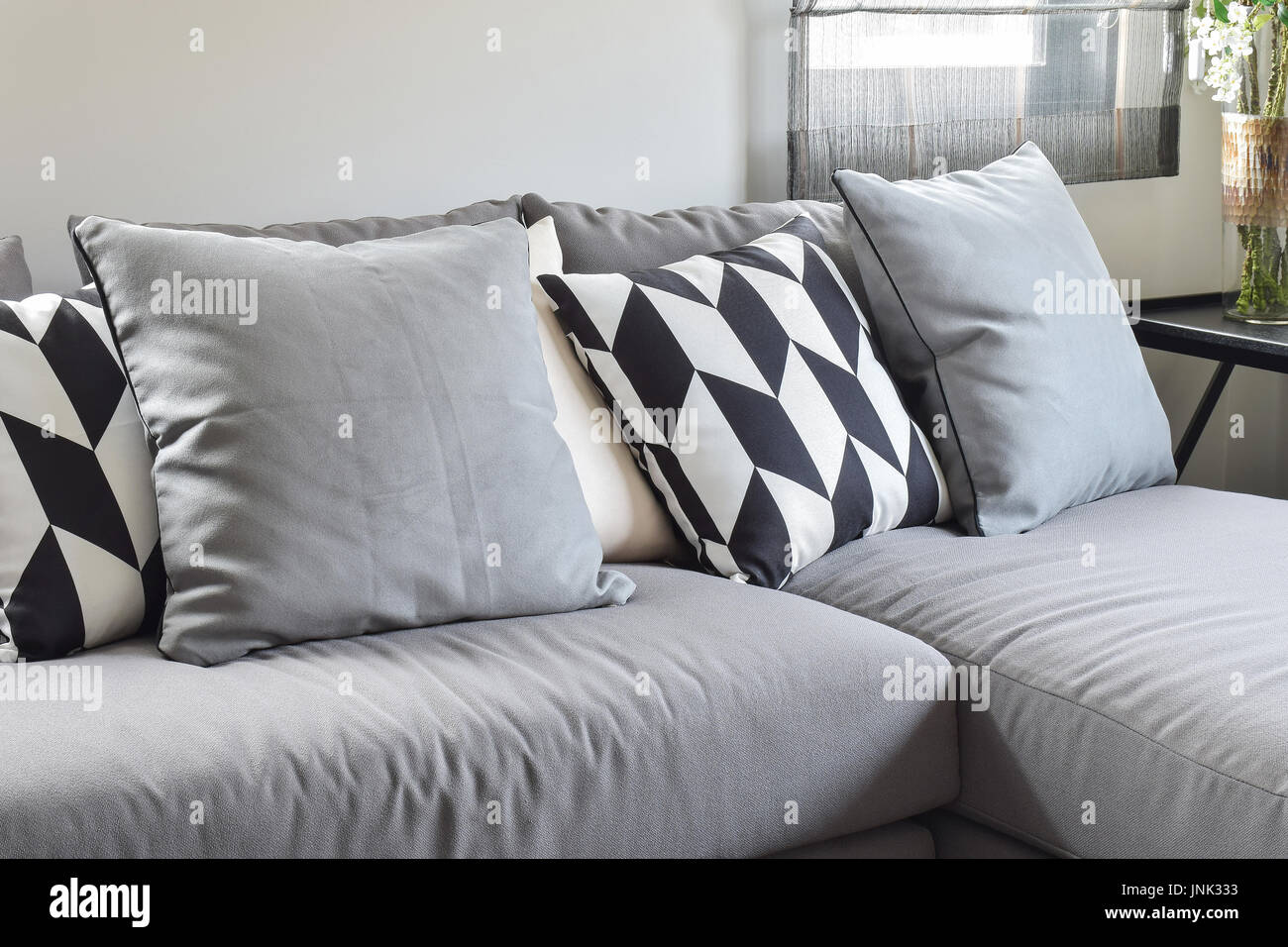 Black and white parallelogram pattern pillows on gray l shape comfy sofa - Stock Image