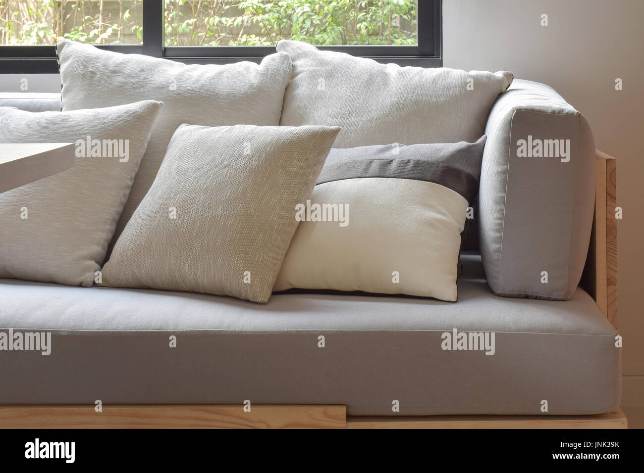Beige varies size pillows setting on light gray comfy sofa - Stock Image