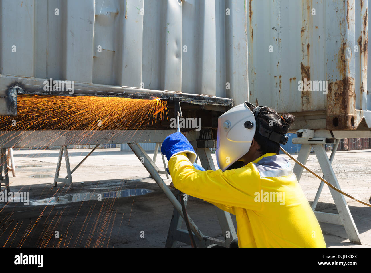 Industry worker with protective mask welding steel to repair container structures manufacture workshop. Worker welding in factory industry. - Stock Image