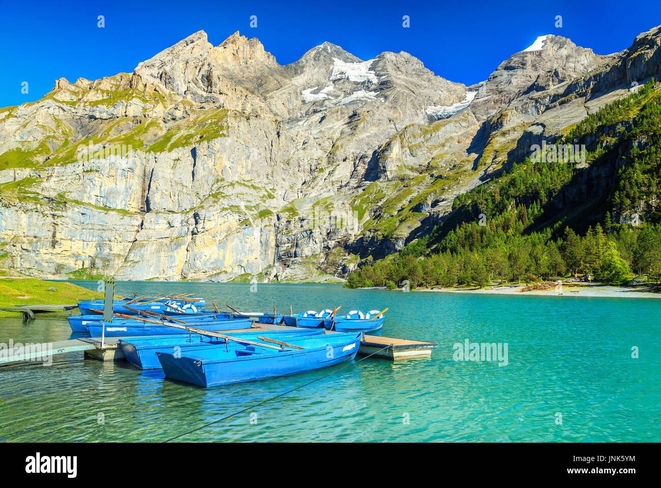 Amazing alpine lake and stunning mountains with blue boats, Oeschinen lake, Bernese Oberland, Switzerland, Europe - Stock Image