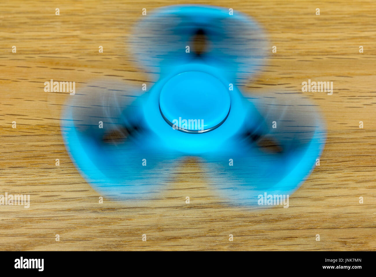 A modern blue (turquoise) fidget spinner rotates quickly and lies on wood - Stock Image