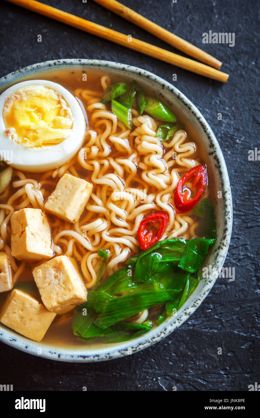 Japanese ramen soup with tofu and egg on dark stone background. Miso soup with ramen noodles and tofu in ceramic bowl, asian traditional food. - Stock Image