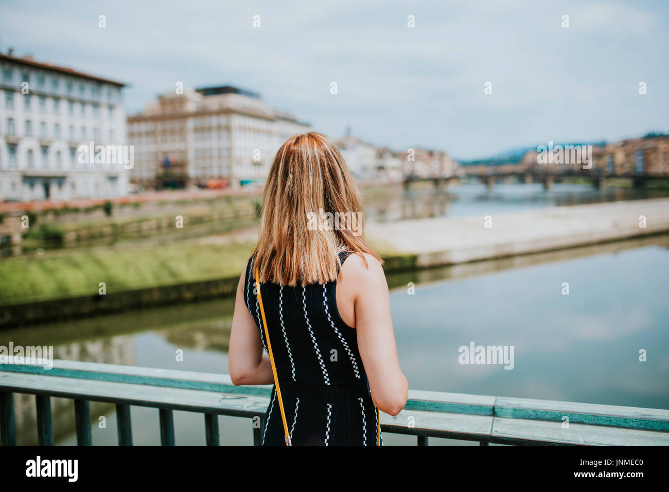 Woman standing on a bridge in Florence - Stock Image