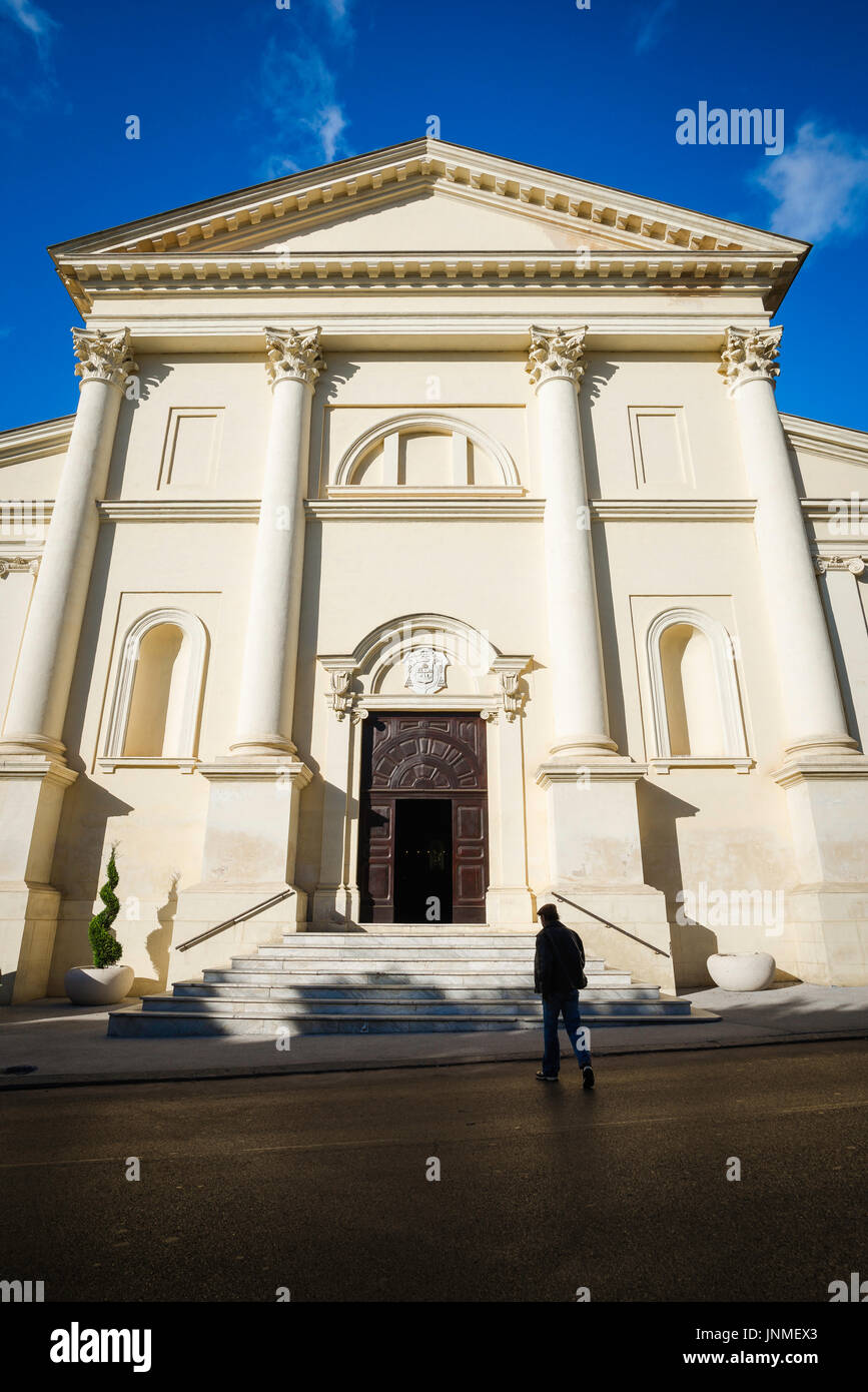 Man church darkness light, a man emerges from dark shadow as he approaches a church in Sassari, northern Sardinia. - Stock Image