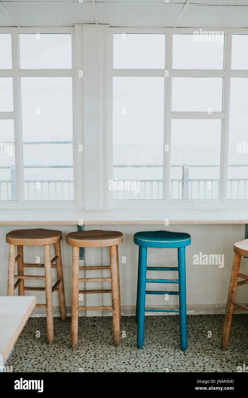 The empty cafe with wooden chairs by the window - Stock Image
