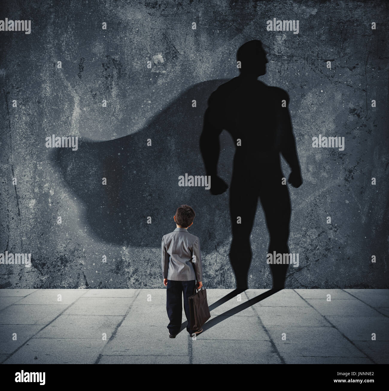 Young businessman with his shadow of super hero on the wall. Concept of powerful small man - Stock Image