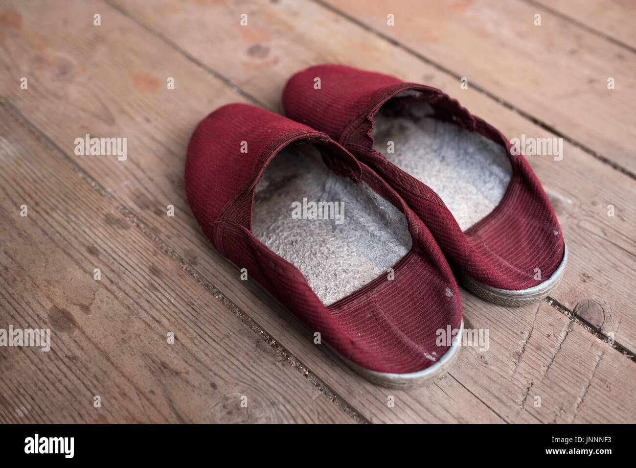5b6649feca7 Warm red slippers on the background of old wooden floor. - Stock Image