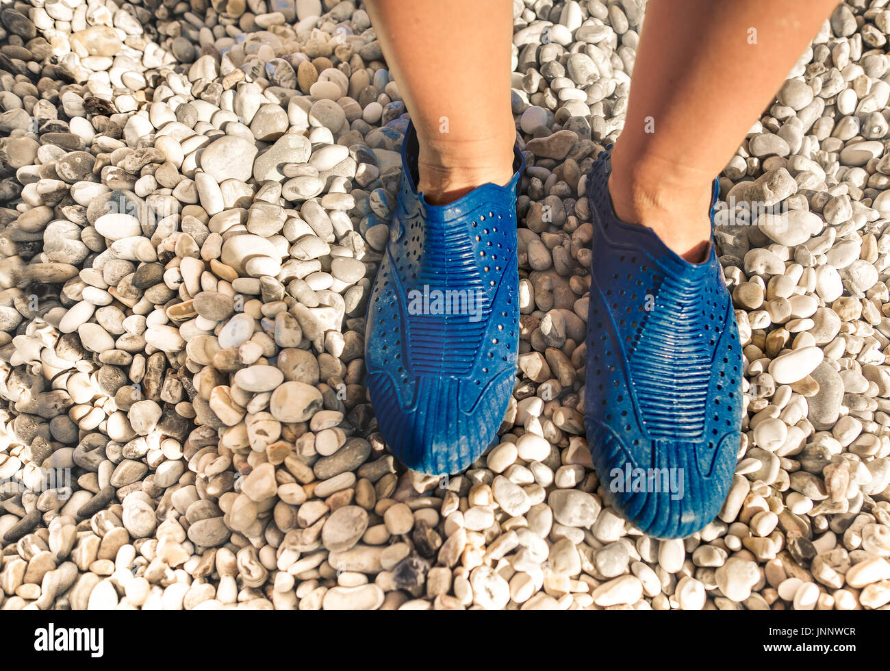 swimming shoes on stone beach - Stock Image